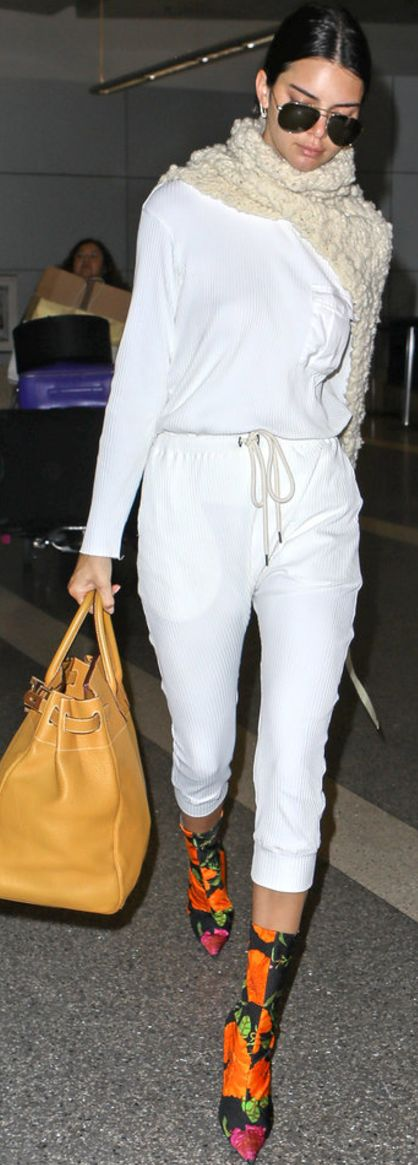 Who made  Kendall Jenner's black aviator sunglasses, white top, pants, floral boots, and tan handbag?