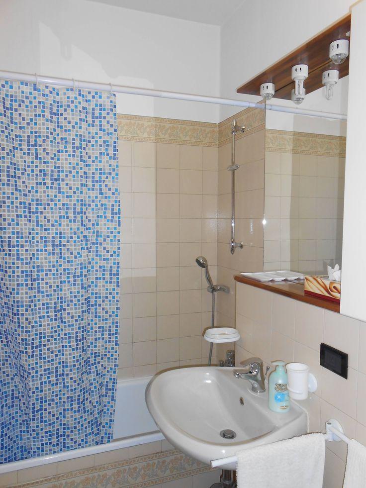 bagno con vasca ed attrezzato con tenda per doccia ha la finestra