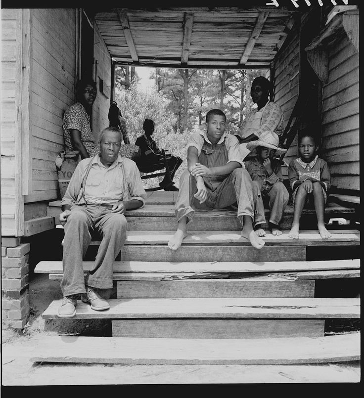 Zollie Lyons, sharecropper, home from the field for dinner at noontime, and part of his family. He has thirteen acres of tobacco and a labor force of five. Upchurch, Wake County, North Carolina.  Photo by Dorothea Lange