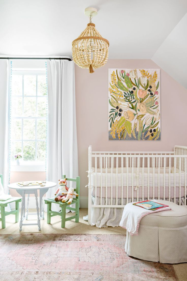 Pastel nursery, white crib, blush pink walls, wooden bead chandelier, oversized floral painting