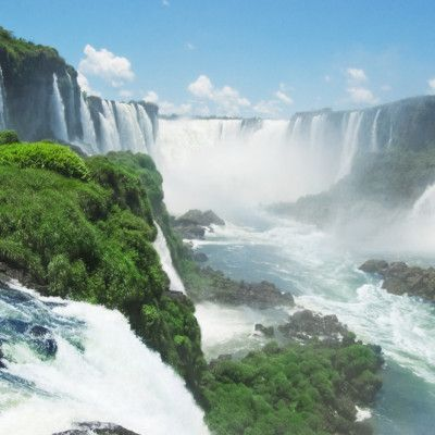 """Iguazu Falls is the beautiful center piece of Iguazu National Park. It is a set of amazing water falls ranging from 60 to 82 meters high on the Iguazu River. The image of these wondrous falls are unforgettable. They are what draws so many people into Iguazu National Park each year. It has been awarded the """"New Seven Wonders of Nature"""" by the New Seven Wonders of the World Foundation."""