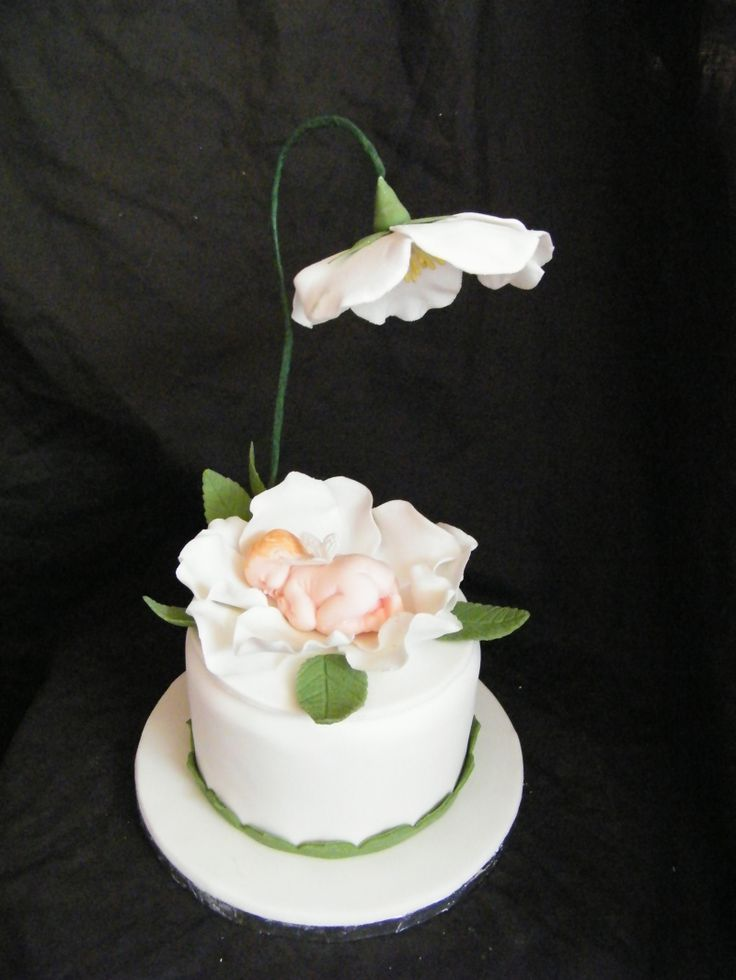 all white cake with a precious baby sleeping inside the flower