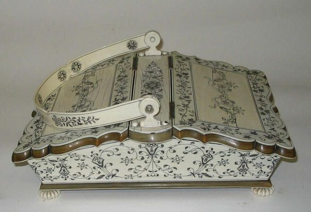 A fine late 18th/early 19th century ivory sewing box Of basket form, the exterior veneered in ivory, engraved and black filled with flowers, leaf branches and scrolls, the hinged centre carrying handled flanked by sloping hinged lids with shaped edges over tapering sides, on knurled bun feet, the interior with a few accessories and with a decorative fret work divider and further ivory decoration, 32cm wide.