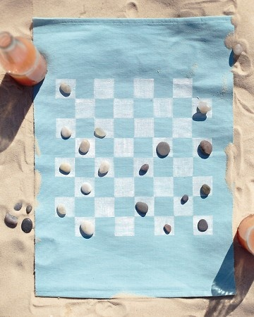 Portable Game Board for the Beach    Make a fun game for the beach using a place mat, fabric ink, and a vinyl eraser.