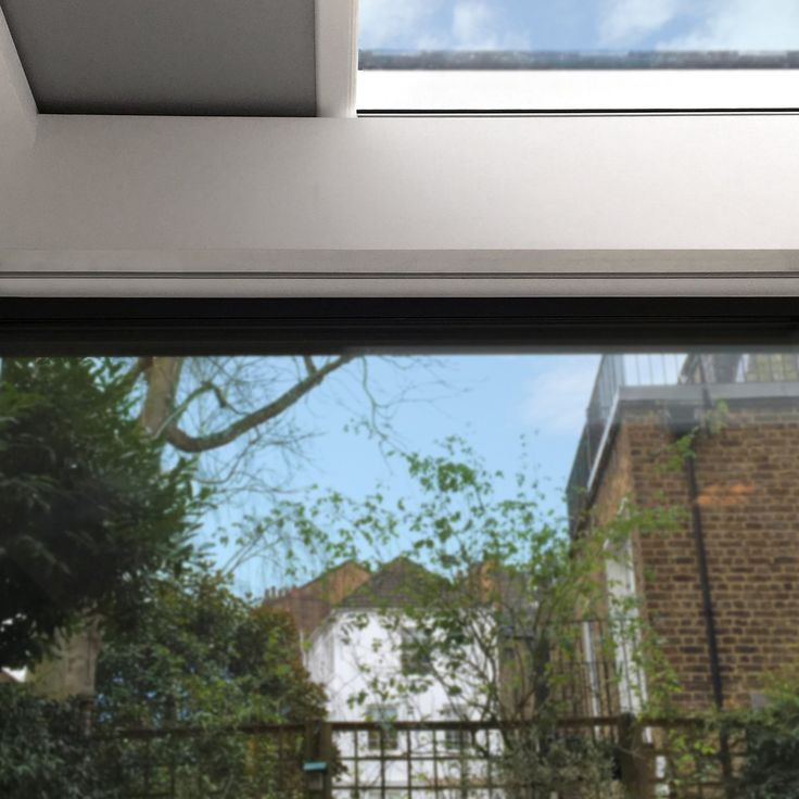 Recessed roller blinds fully concealed in London kitchen extension. Skylight blinds and blinds over bi-fold doors.