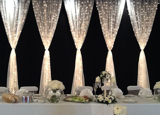 LED curtains make a dramatic impact behind the head table at an indoor wedding reception.