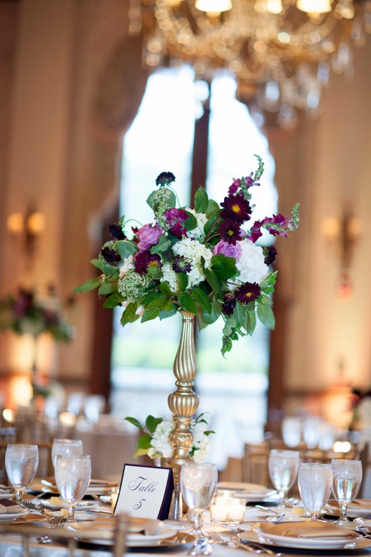 lush purple and lavender reception centerpiece of burgundy dahlia, burgandy scabiosa, lavender roses, queen anne's lace, white hydrangea, burgundy snapdragon and lemon leaf on a tall gold pedestal.
