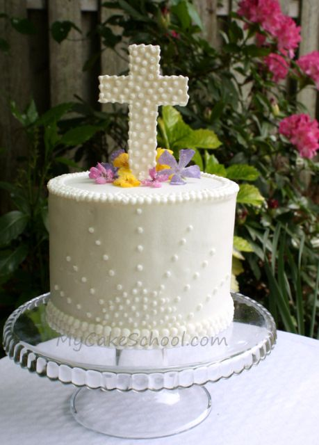 Easter cake.  Real flowers dipped in eggwhites/sugar, gumpaste cross.  Love the sunrise detail on side of cake