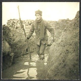 The soldier continues wading along the water-filled trench.