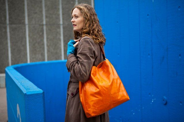 large orange leather handbag and peacock cashmere wristwarmers