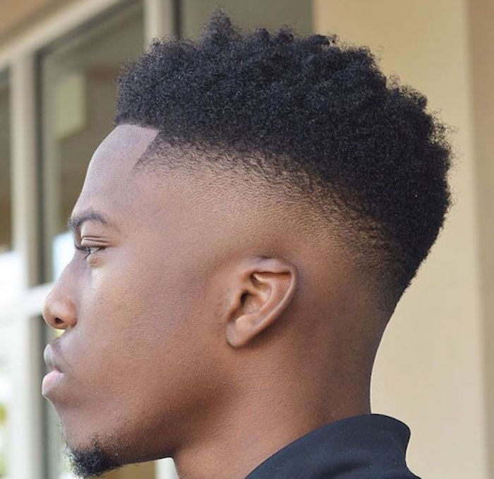 faded undercut, young man with faded Afro hairstyle, very short shaven on the side and longer and curly on top, small beard and a black top