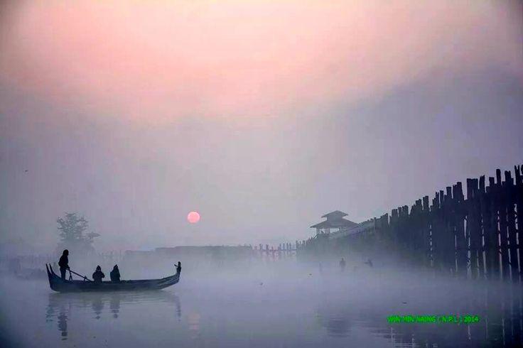 Boating by a misty sunset near the famous U Bein Bridge (World's longest teak bridge) on Lake Taung Tha Man in Amarapura, Myanmar.