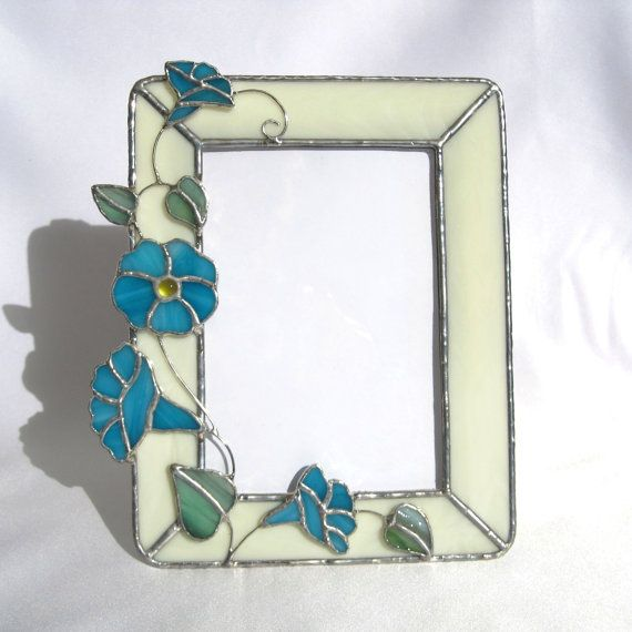 Morning Glories Stained Glass Picture Frame by hobbymakers  Morning Glories blooming are a a sure sign of spring.  It's designed to hold a 5 x 7 photo.  36 hand cut pieces of stained glass, one glass nugget and copper wire.   It is designed to hold a 5 x 7 picture and can sit or hang on a wall. Wire was used to connect the flowers and create the vine. Clear glass is incorporated into the design to cover the photo you add. U channel zinc is attached to the back to hold a cardboard easel back.