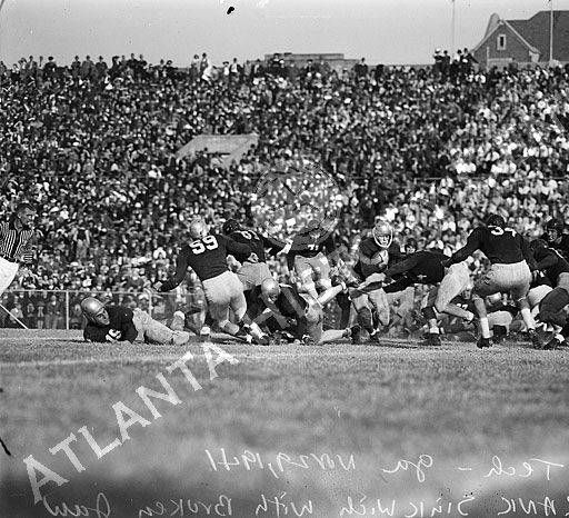 View of a football game between the University of Georgia and Georgia Tech showing UGA player Frank Sinkwich (with football) at Grant Field in Atlanta. GA Institute of Technology or GA Tech was founded in 1885 to help the state move beyond its agrarian roots. The institution opened in 1888 as a trade school, but became a nationally recognized technological university. The college is part of the University System of GA. The campus is 2 miles north of downtown Atlanta. Atlanta History Center.