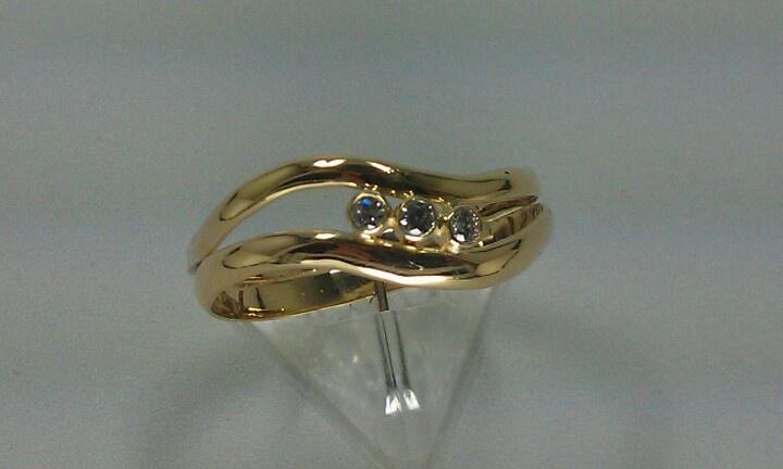 Ring gemaakt van twee trouwringen, gemodelleerd in een golf en voorzien van drie zirkonia's, gladom gezet.