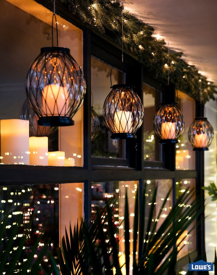Hanging lights add a festive air to any setting and create an additional level of light. Battery-operated indoor lanterns are suspended in the home but shine through windows to cast a flickering glow onto the porch.
