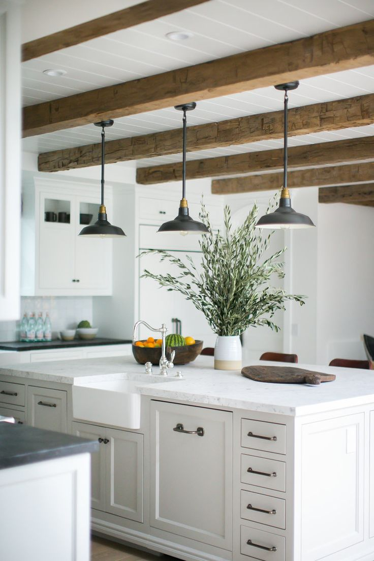 Rustic beams and pendant lights over a large kitchen island