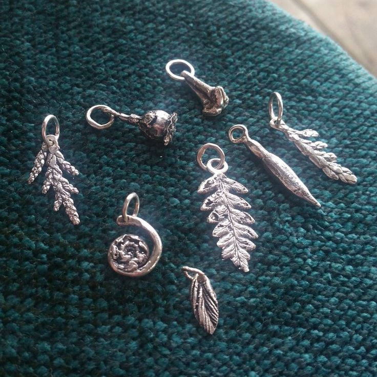 A closer look at some of the tiny stocking stuffer charms: for charm bracelets, charm necklaces, and mismatched earrings. Silver chains and earring hooks will be available at Manson's craft fair November 25. #charms #charmbracelet #etsyca #naturejewelry #organiccasting #lostwaxcasting #cortesisland #charmnecklace #mismatched #mismatchedearrings