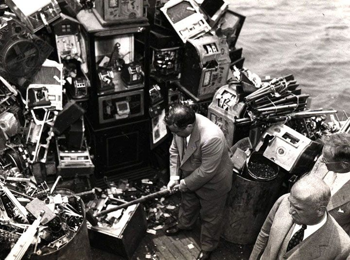 In Focus - Historic Photos From the NYC Municipal Archives - The Atlantic Aboard a police boat on October 10, 1934, New York Mayor Fiorello LaGuardia hacks away at confiscated slot machines about to be destroyed and dumped into New York harbor.