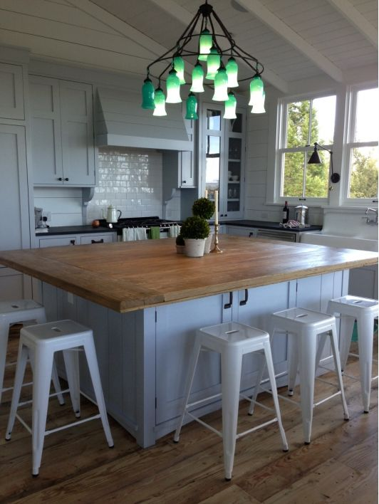 Kitchen with wooden island table. Oversized kitchen islands are the peak of chic in southern kitchen design this year.