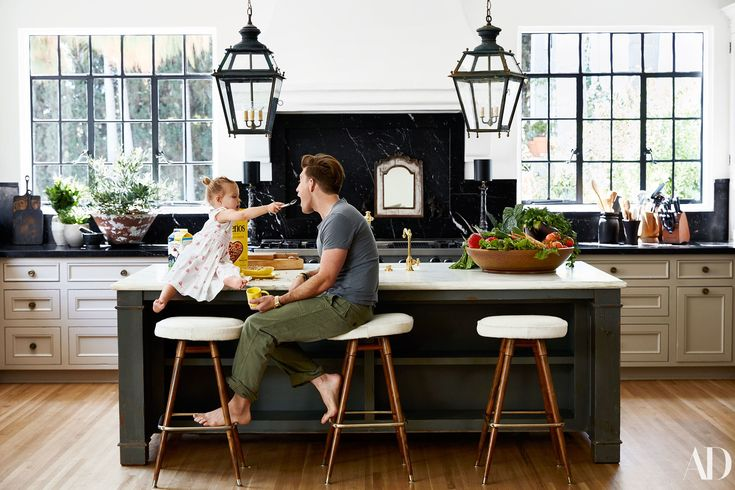 Step Inside Berkus ad Brent's Gorgeous LA Home | Brent and Poppy (wearing a D. Porthault dress) at the kitchen island; circa-1960 French barstools; sink fittings by Waterstone; 19th-century French lanterns. Backsplash and surrounding countertops by Ollin Stone; Whitechapel brass knobs.
