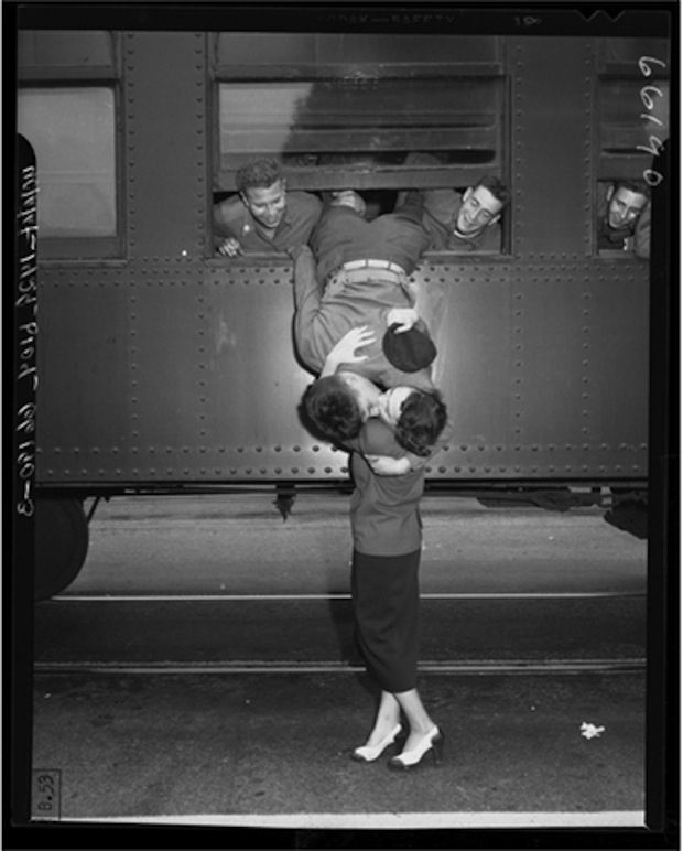 This picture of a California National Guardsman hanging out the window of his train, kissing his wife good-bye in 1950