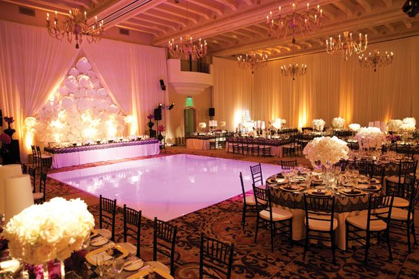 Rose-tinted lighting washes over the glossy floor, casting guests in a flattering glow.
