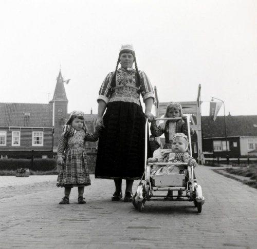Vrouw met kinderen en een kind in een kinderwagen in Marker klederdracht. Marken, Nederland, april 1961