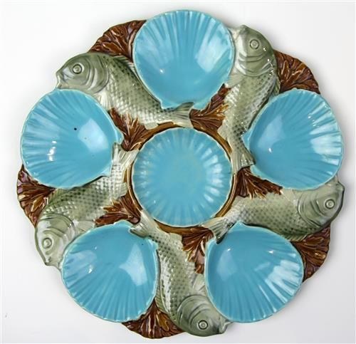 Minton Majolica Oyster Plate decorated with five spiralling fish on a brown ground & six turquoise shell form dishes.