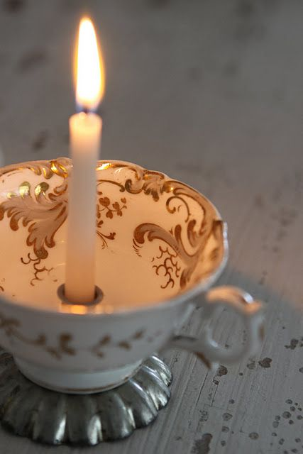 Old tea cup with candy mold glued on the bottom and candle cup