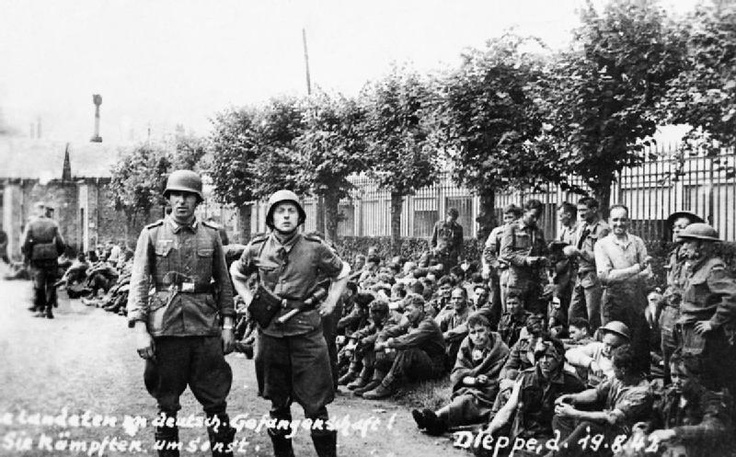 Allied prisoners rest by the roadside, guarded by Germans, Dieppe.