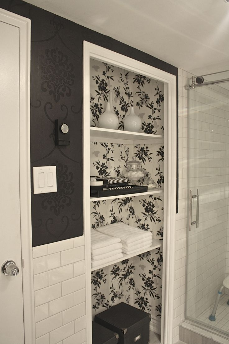 We used vintage style black baroque wallpaper paired with dazzling porcelain white subway tiles to create a dramatic first impression. We also removed the closet doors on the bathroom storage closet and used a beautiful black, grey and white floral print wallpaper to create a display area that is functional but still pretty.