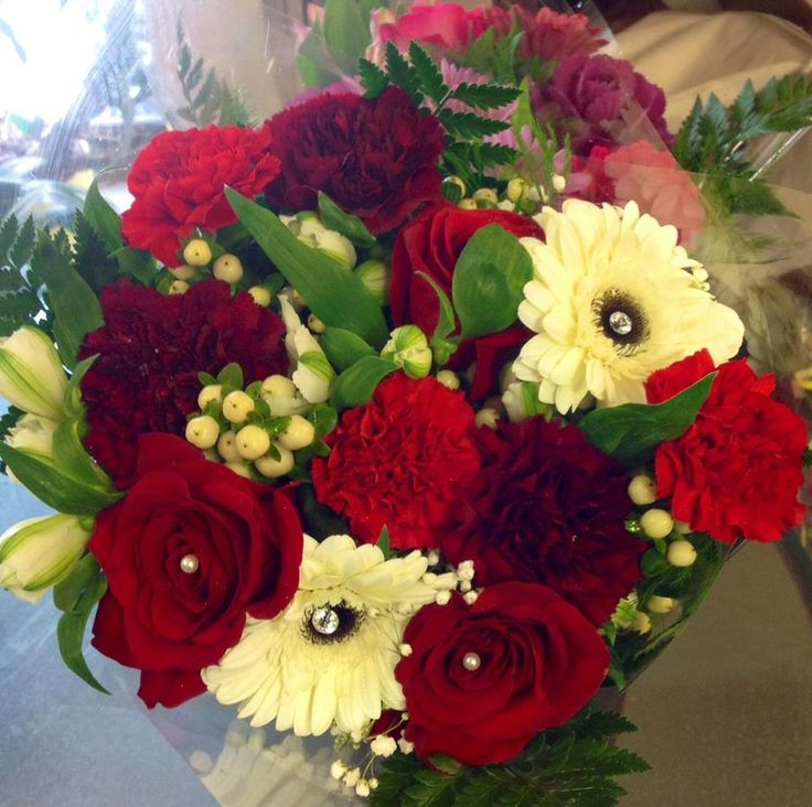 Very romantic mixed bouquet filled with elegant red roses and deep red carnations, as well as cream gerberas decorated with white gem stones.