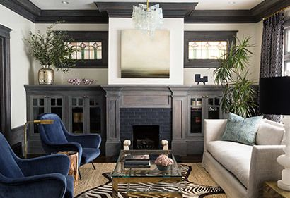 Blue velvet swoopy armchairs modernize a Craftsman style living room with dark wood built-ins.