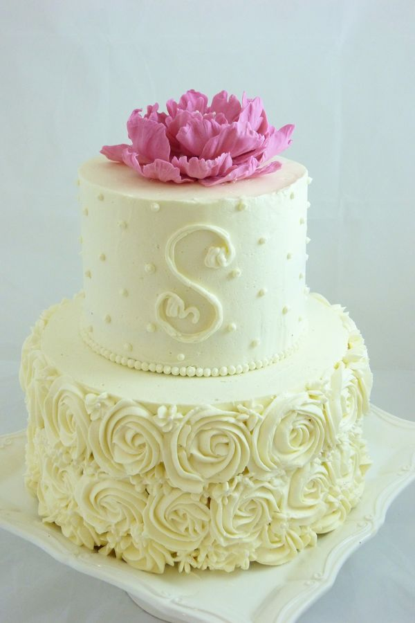 Buttercream decorated small wedding cake with piped roses, dots and a monogram. Handmade gum paste peony on top.