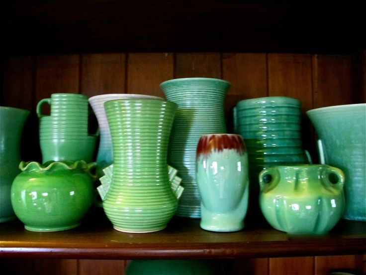 Liz's green pottery collection: LOVE the art deco vase at the back on the left