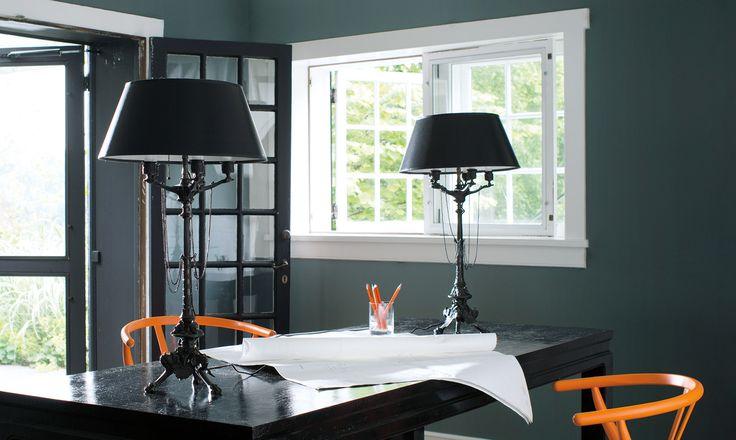 Bureau à domicile contemporain aux murs vert foncé, porte-fenêtre et chaises orangées appariées.