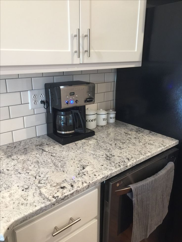 White Ice Granite, White Subway Tile With Gray Grout.