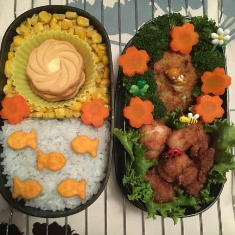 #105 Alifa USA  My bento is a spring time bento, with the sun coming up over a lake full of happy fishes. The sun's happy rays are making all the bees and lady bugs come out to enjoy the rays, and the flowers are blooming to feel the sun on their face.   Sun: Lemon Cookies (Dessert piece)  Fried Chicken Carrots Broccoli Rice Corn