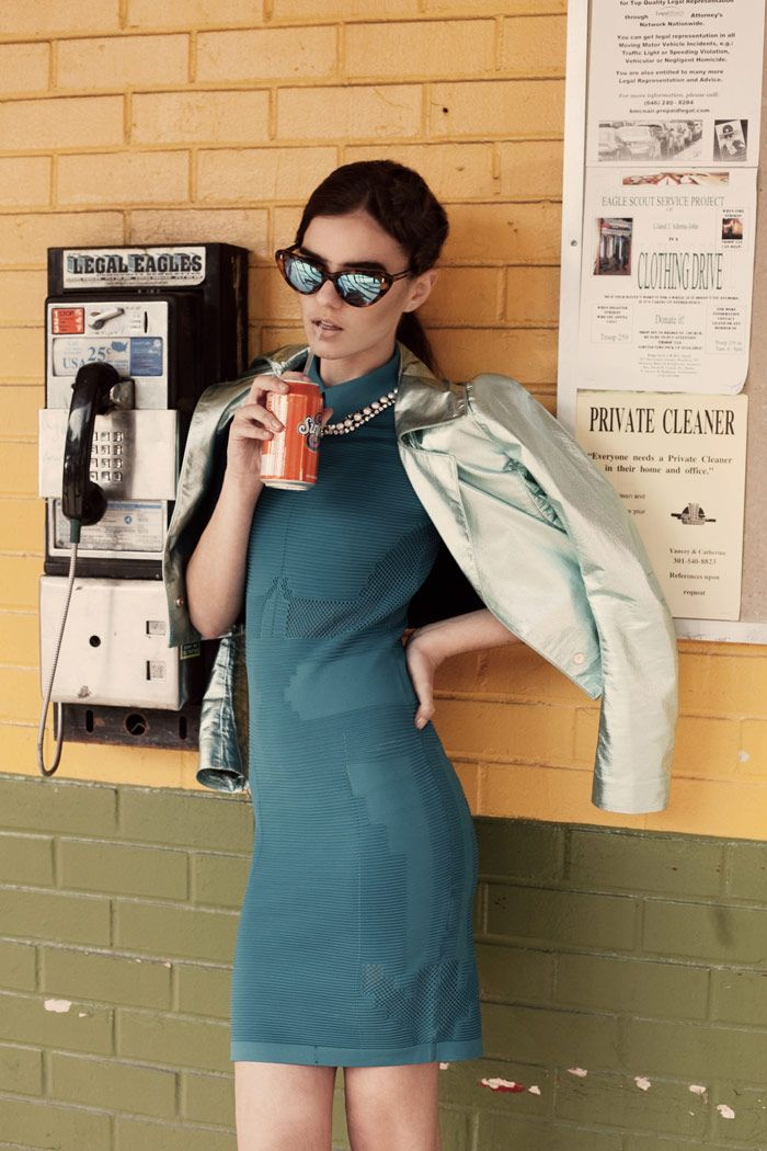 young woman with sunglasses sipping on a soda next to a payphone
