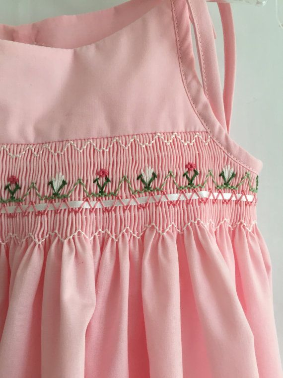 """Dainty Pink Tie Dress! – Size 18 mo This size 1 Pink Dress is handsmocked, using DMC threads, in white and deep pink flowers. A row of 1/4"""" double white satin ribbon is woven into the DMC threads underneath the flowers. The dress has adjustable ties, which allow room for growth. The back has two white heart buttons. And the blouse is included, which gives you two dresses! The fabric is easy to care for polyester/ cotton. All materials have been pre-shrunk. Machine wash and tumbl..."""