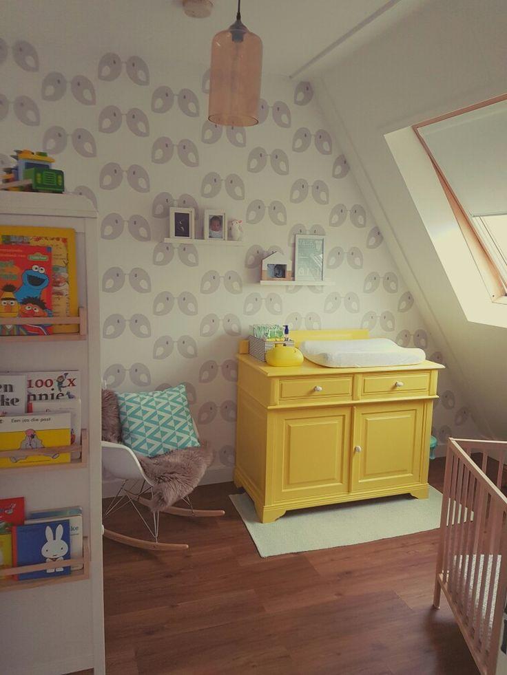 Gele commode als eyecatcher in de babykamer. Behang met vogeltjes van Tis Lifestyle. Kruidenrekjes van Ikea als boekenplank. Schommelstoel met schapenvacht van Ikea.
