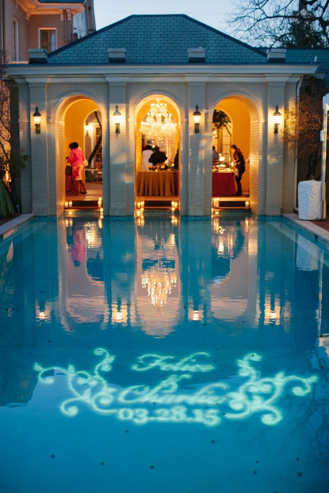 frenzelstudios.com An East Ivy Mansion destination wedding venue reception, with pin monogram lights reflected on a swimming pool; with Randi Events, Enchanted Florist & Bright Event Productions