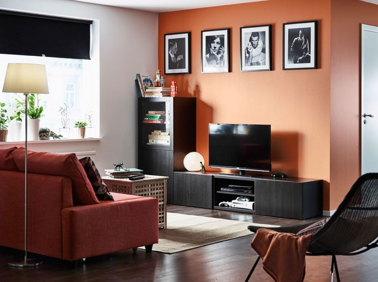 A second living room with a TV bench in black-brown with drawers, doors and tempered glass door. Shown together with a dark orange corner sofa-bed and a storage table in acacia.