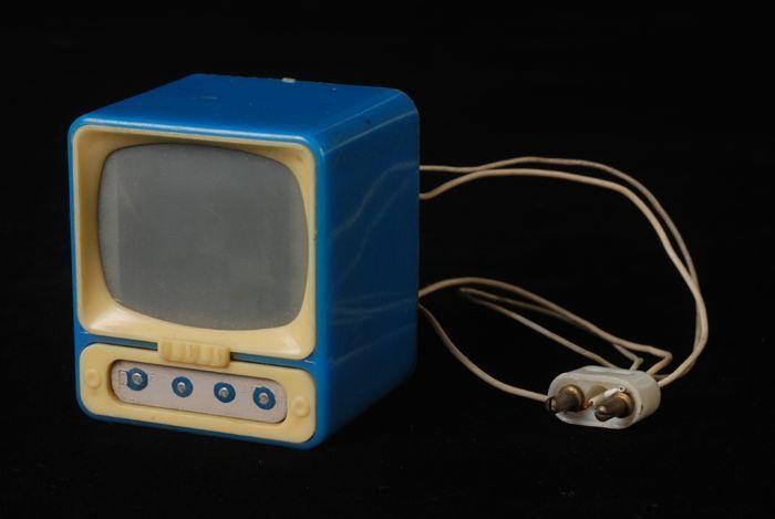 """Blauw met witte miniatuur televisie met lampje ingebouwd zodat scherm echt oplicht, waarbij dia zichtbaar wordt, met snoer en stekker, bij poppenhuis """"Ria"""" - Museum Rotterdam"""