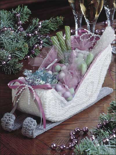 """Victorian Sleigh Create this sleigh to hold holiday candy for your guests. This e-pattern was originally published in Crochet Holiday Collection. Size: 5"""" tall. Made with medium (worsted) weight yarn, 7-count plastic canvas and hook sizes E (3.5mm) and F (3.75mm). Skill Level: Intermediate Designed by Rosemary Walter"""