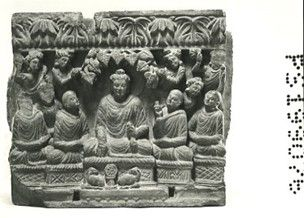 Panel showing the First Sermon. The seated and haloed Buddha, wearing an over-robe over both shoulders and with a curved neckline in relief, touches the seat with his right hand and secures the robe above his lap in his left hand, from which the gathered drapery spreads in the usual way. The folds are defined by grooves. The Buddha's head is oval with sharp-cut features