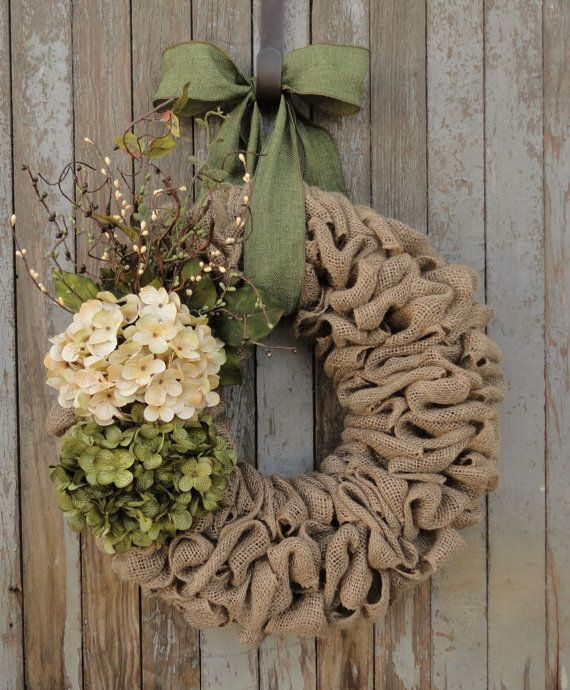 Beautiful earth-tone Easter wreath. Cream and green hydrangea flowers are perfectly coordinated with cream, green, and brown pip berries, greenery, and curly willow twigs. Flowers and accents are attached to your choice of a natural burlap wreath base, twisted wooden rattan wreath base, or a natural grapevine wreath base. Hangs by either a brown or moss green faux burlap ribbon. Our beautiful wreaths make unique gifts for weddings, birthdays, Christmas, and Mothers Day. This wreath is made…