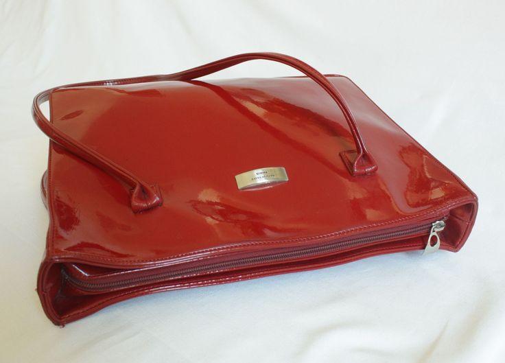 """Rubína - kabela z lesklé imitace kůže """"Rubína"""" je dámská byznys kabelko-taška z rubínově červené imitace lakové kůže. Tvarově je jednoduchá a přitom je elegantní. Kabelka má dvě dlouhá našitá ucha na nošení přes rameno. Uzavírá se v horní části zipem. Vnitřek je ze šedobéžového omyvatelného plátna. Uvnitř je malá kapsička na zip a větší volně ..."""