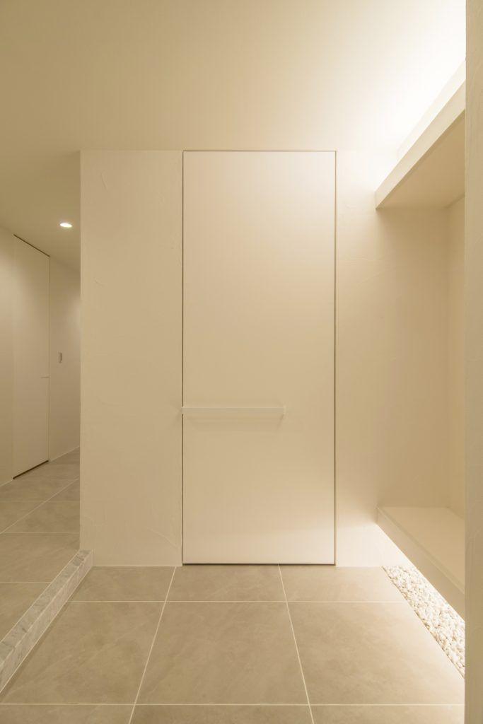 白妙の家 白で統一した玄関はベンチ下に間接照明と玉砂利 玄関 間接